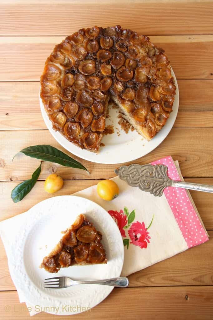 Loquat upside down cake, and a slice of cake served on a white plate with a small cake fork placed over a floral tea towel.