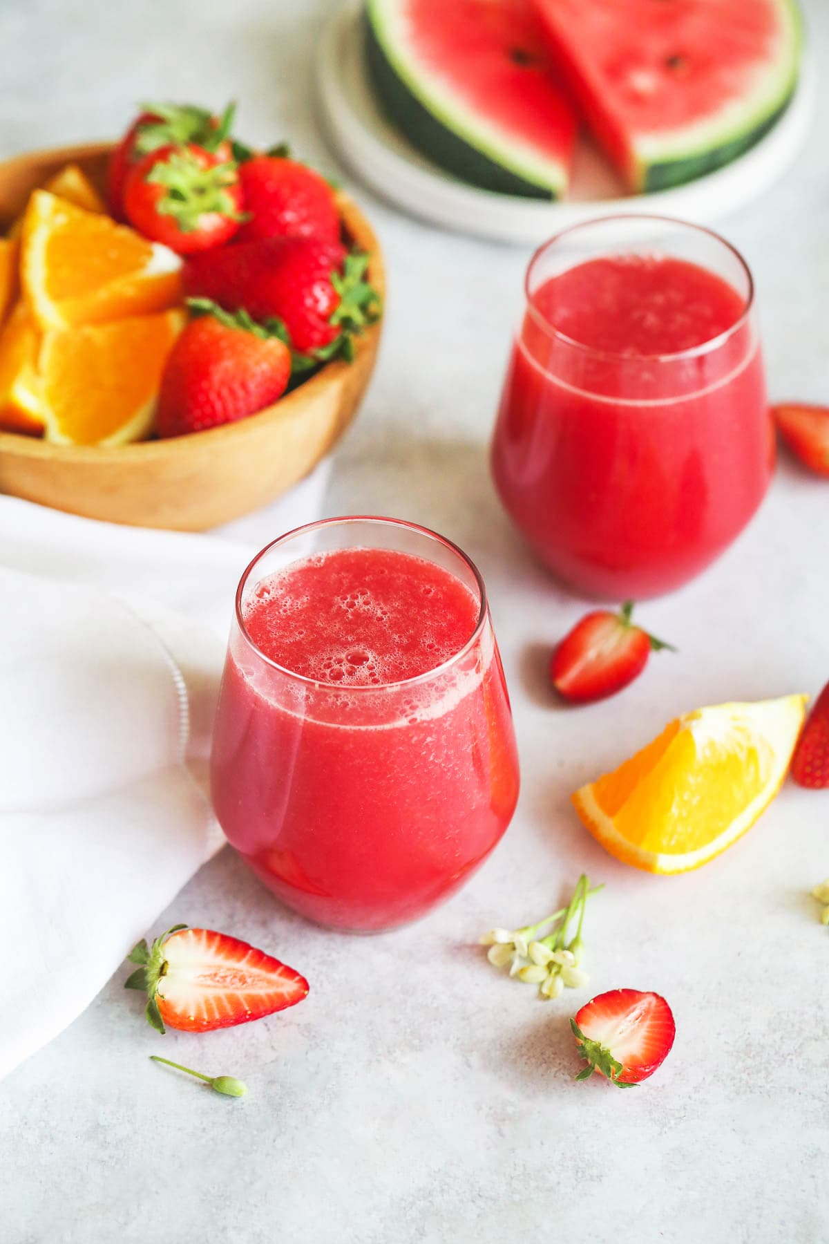 Strawberry Watermelon Smoothie in 2 glasses, and a bowl of fresh strawberries, orange, and watermelon slices.