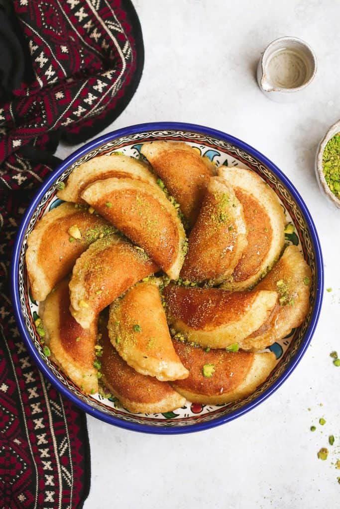 Atayef on a large oriental dish, garnished with ground pistachio