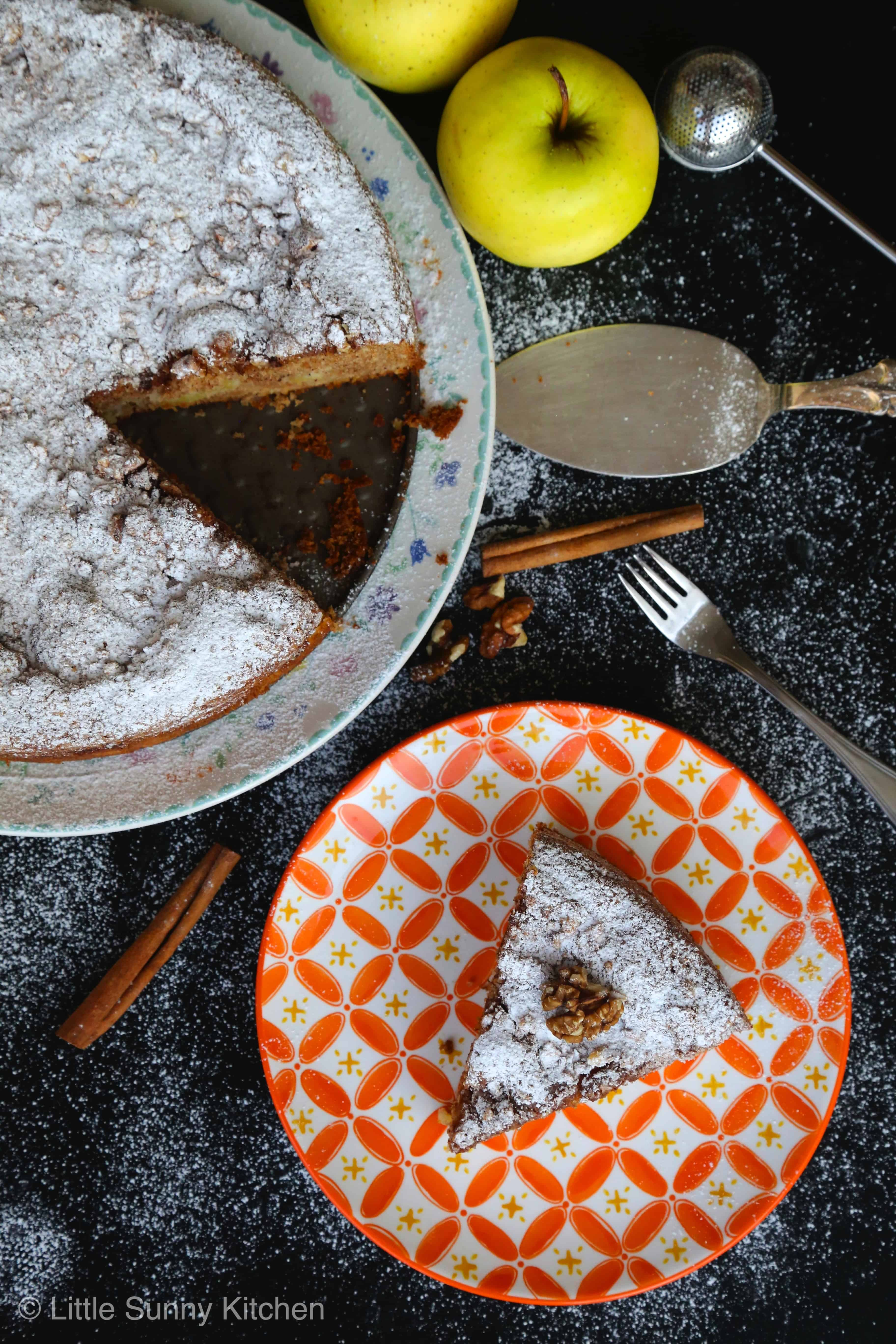 Top view of an apple Sharlotka cake slice served in an orange patterned plate with the cake, cinnamon sticks, and apples on the side.