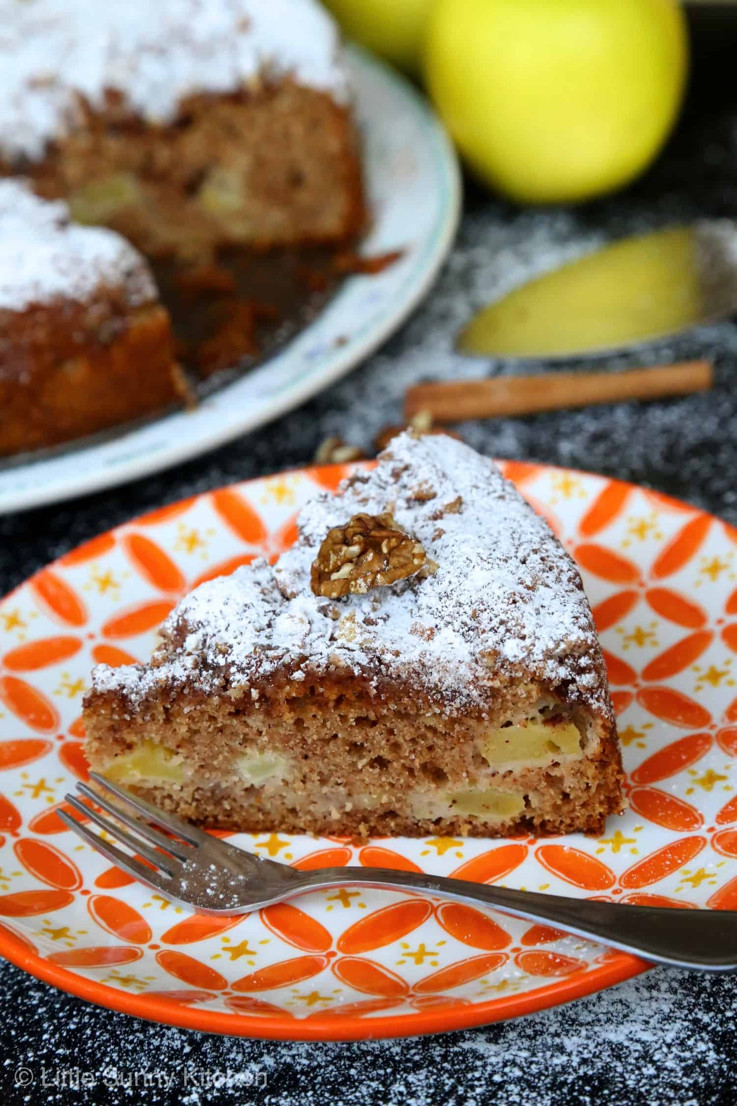 A slice of apple Sharlotka cake topped with powdered sugar served in an orange patterned plate and a fork.