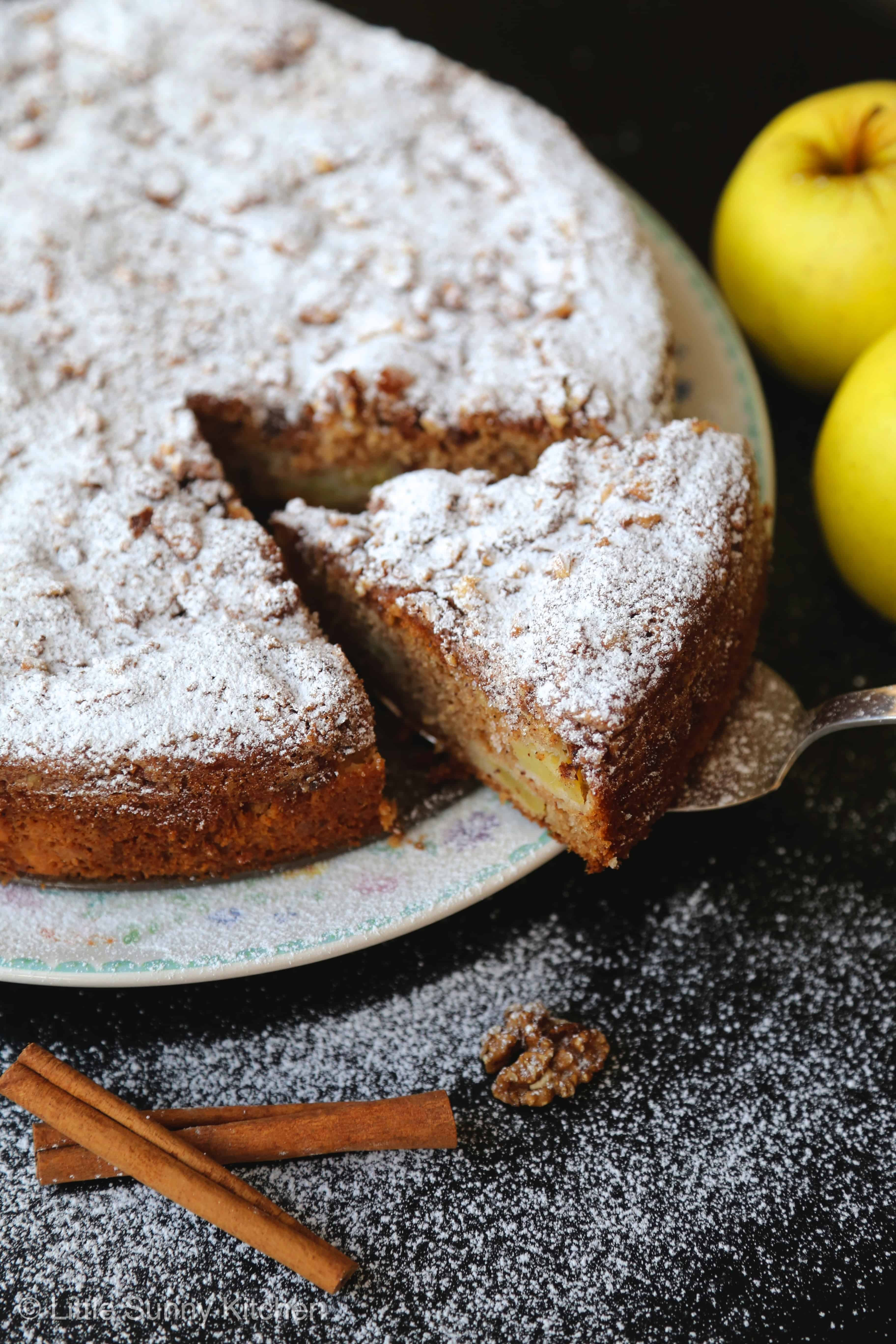 Apple Sharlotka cake topped with powdered sugar with apples and cinnamon sticks on the side.