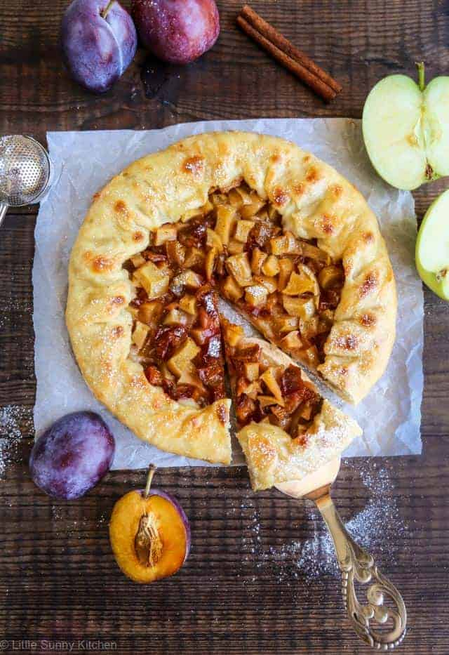 Baked plum apple galette on a parchment on a wooden surface.