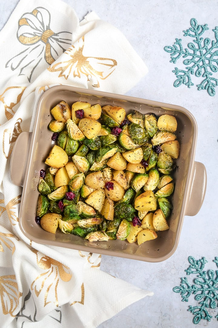 Roasted Brussels Sprouts with Potatoes and Cranberries in a baking ceramic pan, with snowflake ornaments in the background