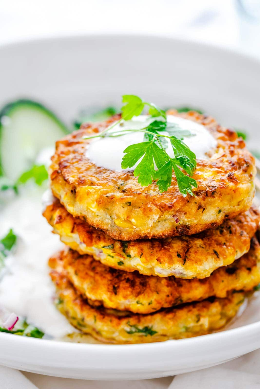 4 corn fritters stacked on each other in a white plate