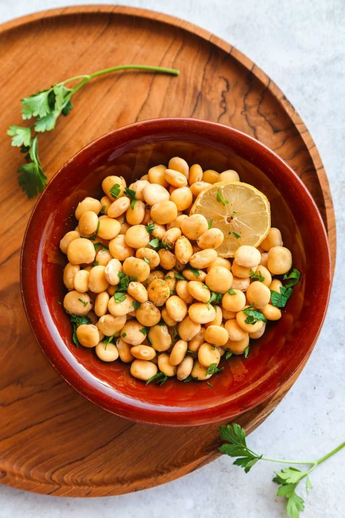 Cooked Lupini beans served with parsley in a traditional middle eastern bowl