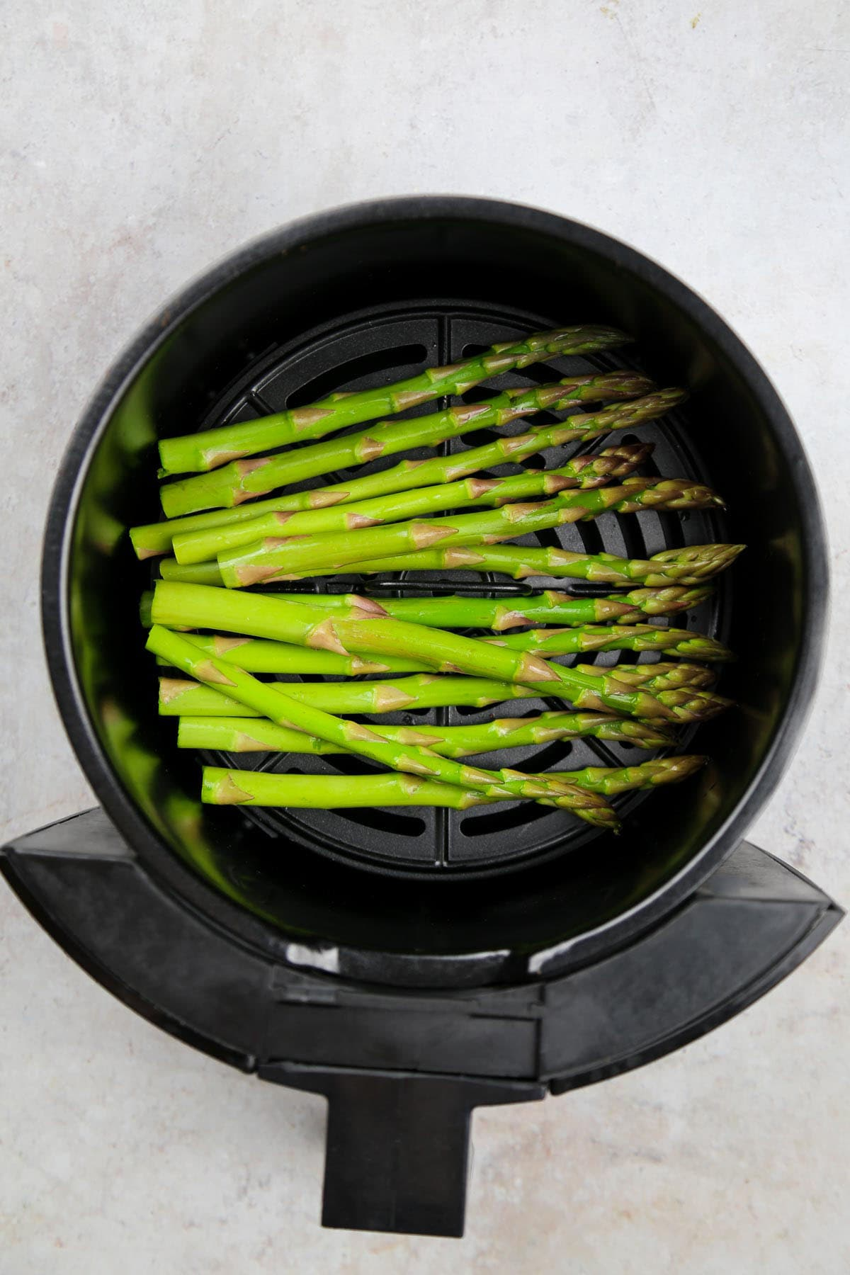 Fresh asparagus tips placed in the air fryer basket