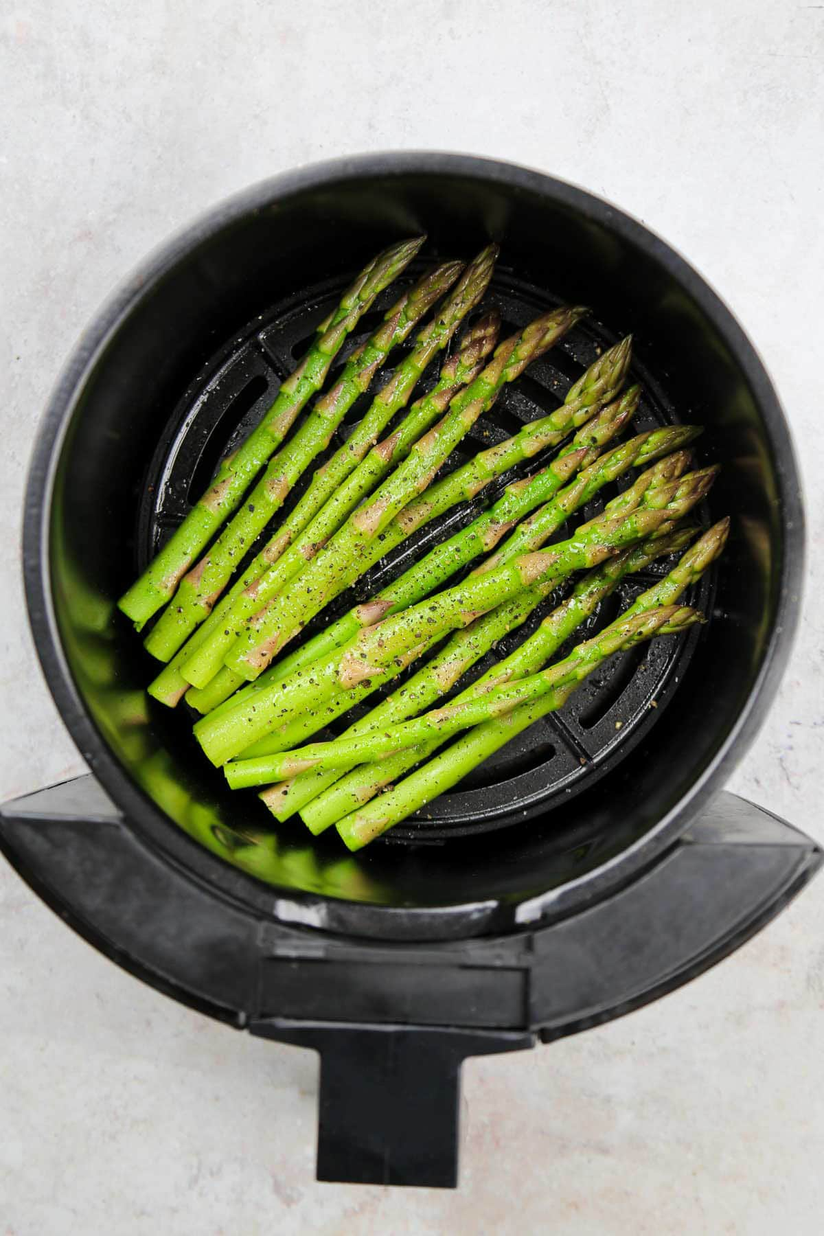 Seasoned and oil-sprayed asparagus tips in the air fryer basket.