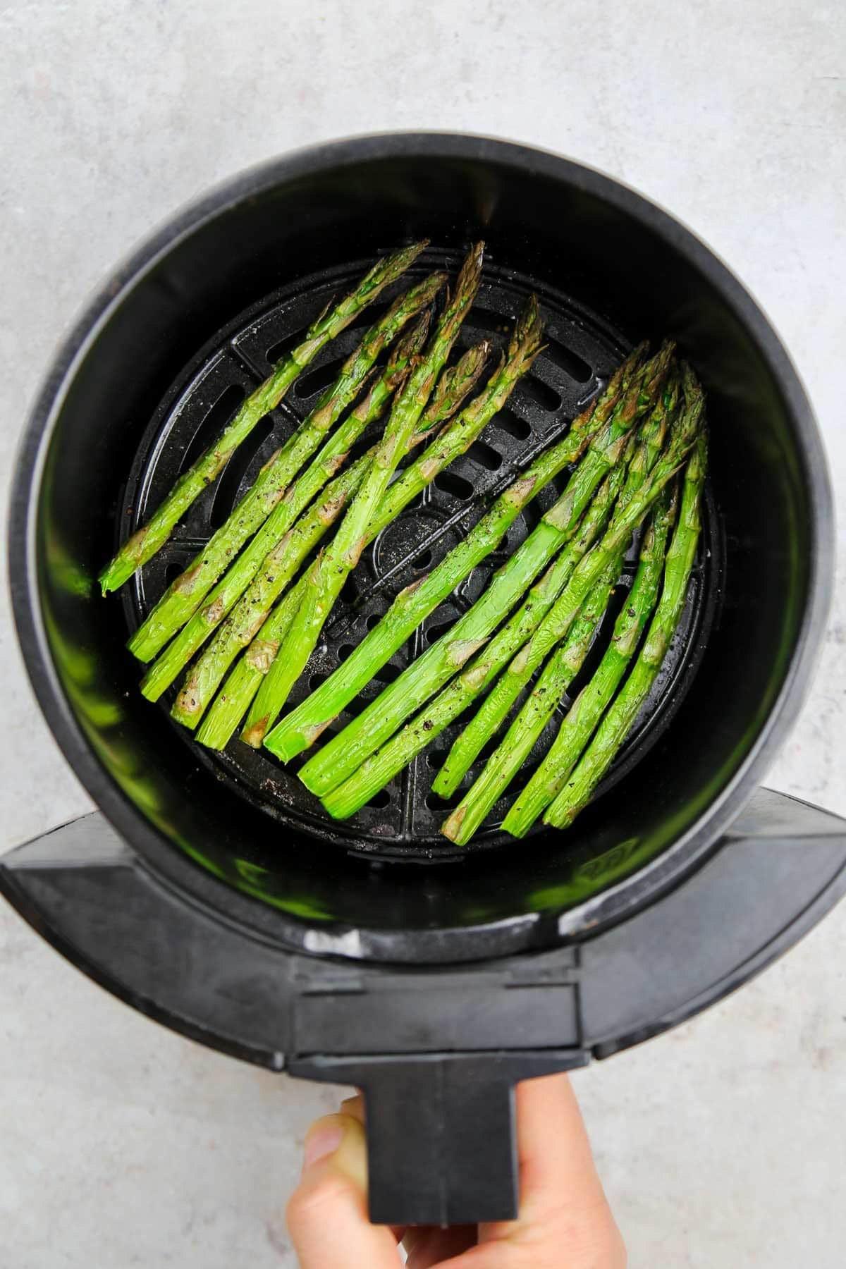 Ready and crispy asparagus in the air fryer basket.