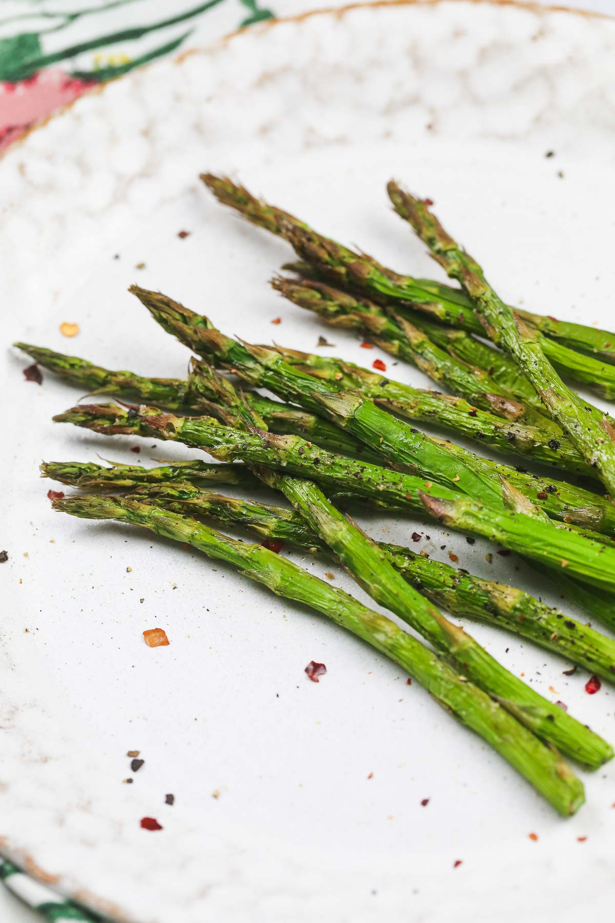 Air Fried asparagus tips topped with chilli flakes on a white plate