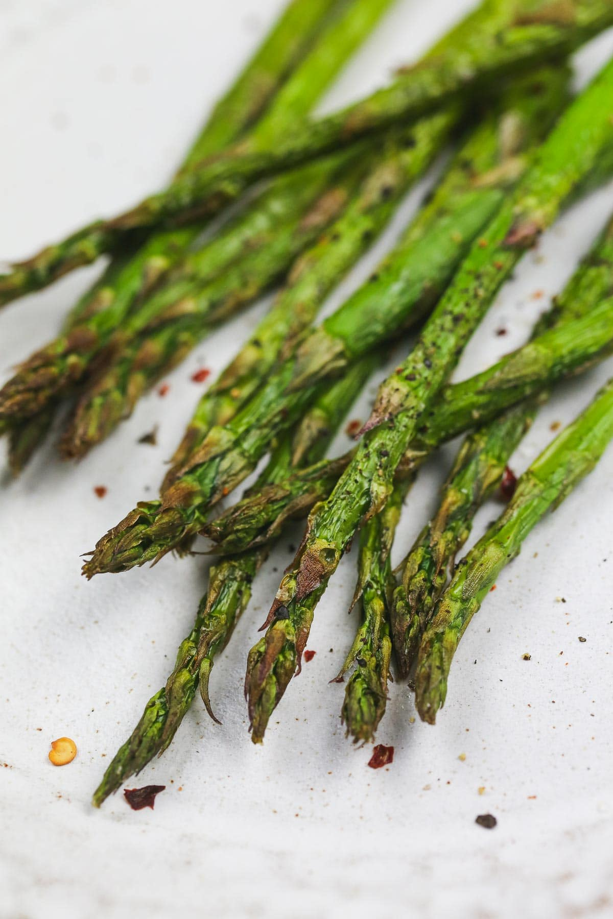 A close up shot of crispy asparagus with chilli flakes.