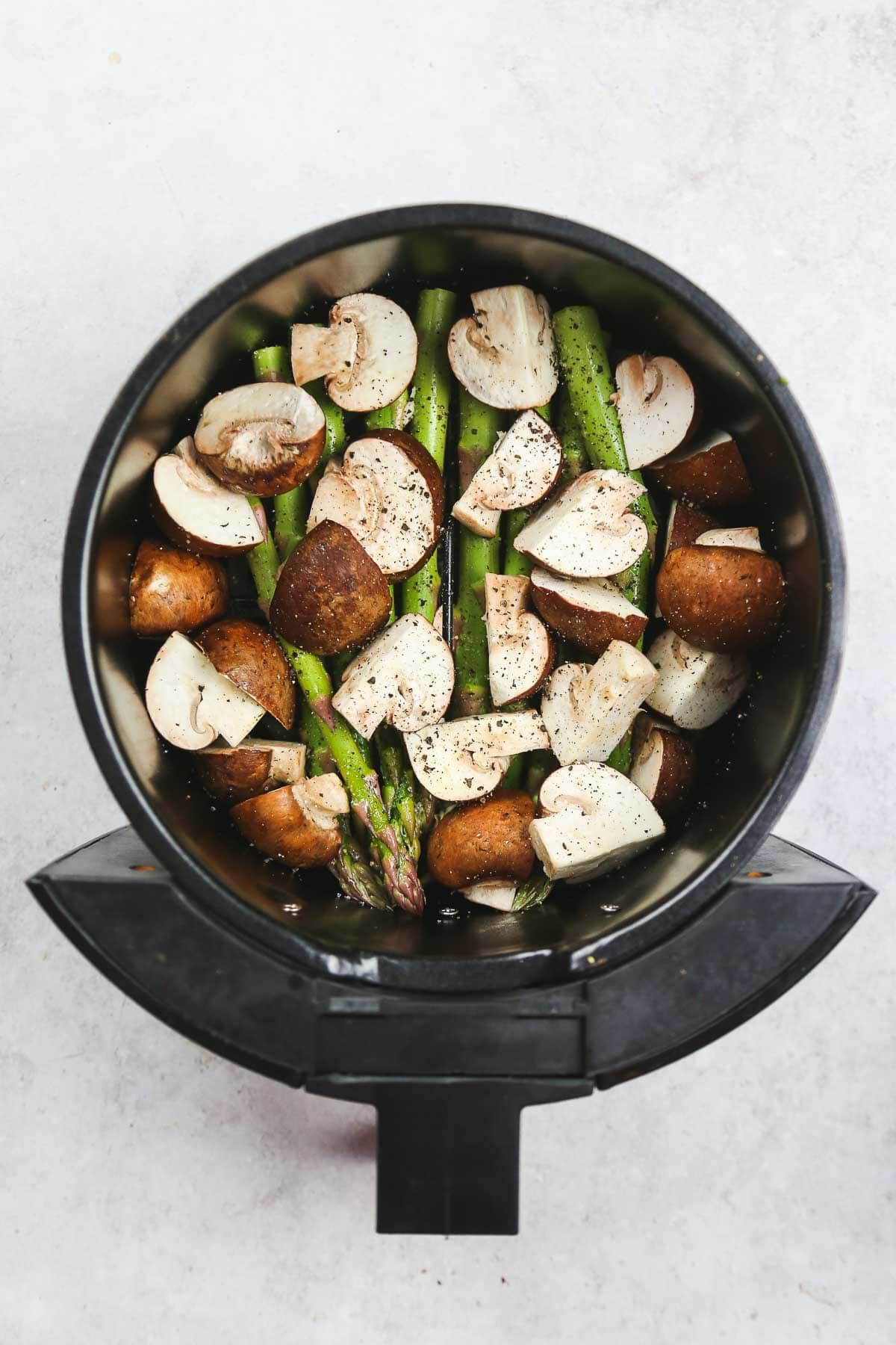 Seasoned and oil-sprayed asparagus and mushrooms placed in the air fryer basket.
