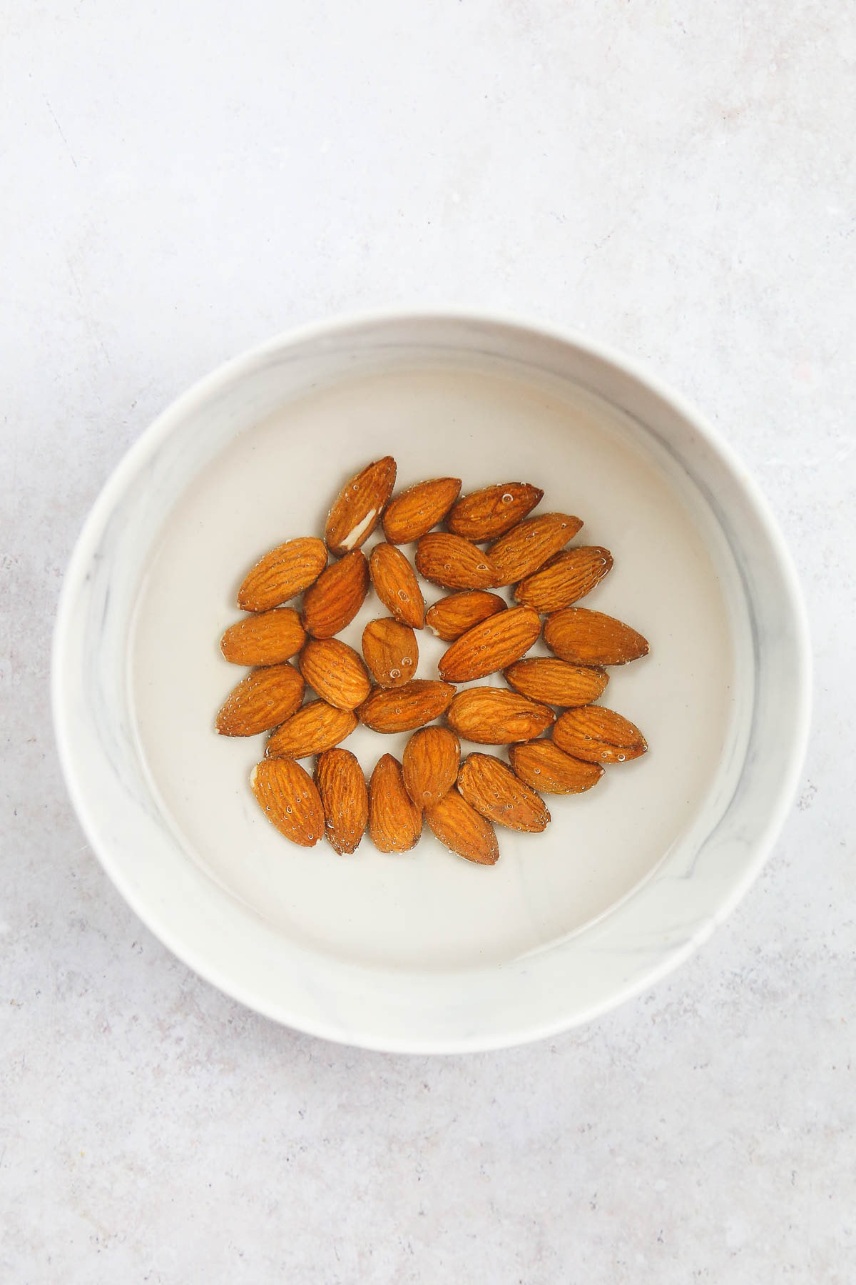Almonds soaked in water in a white bowl.