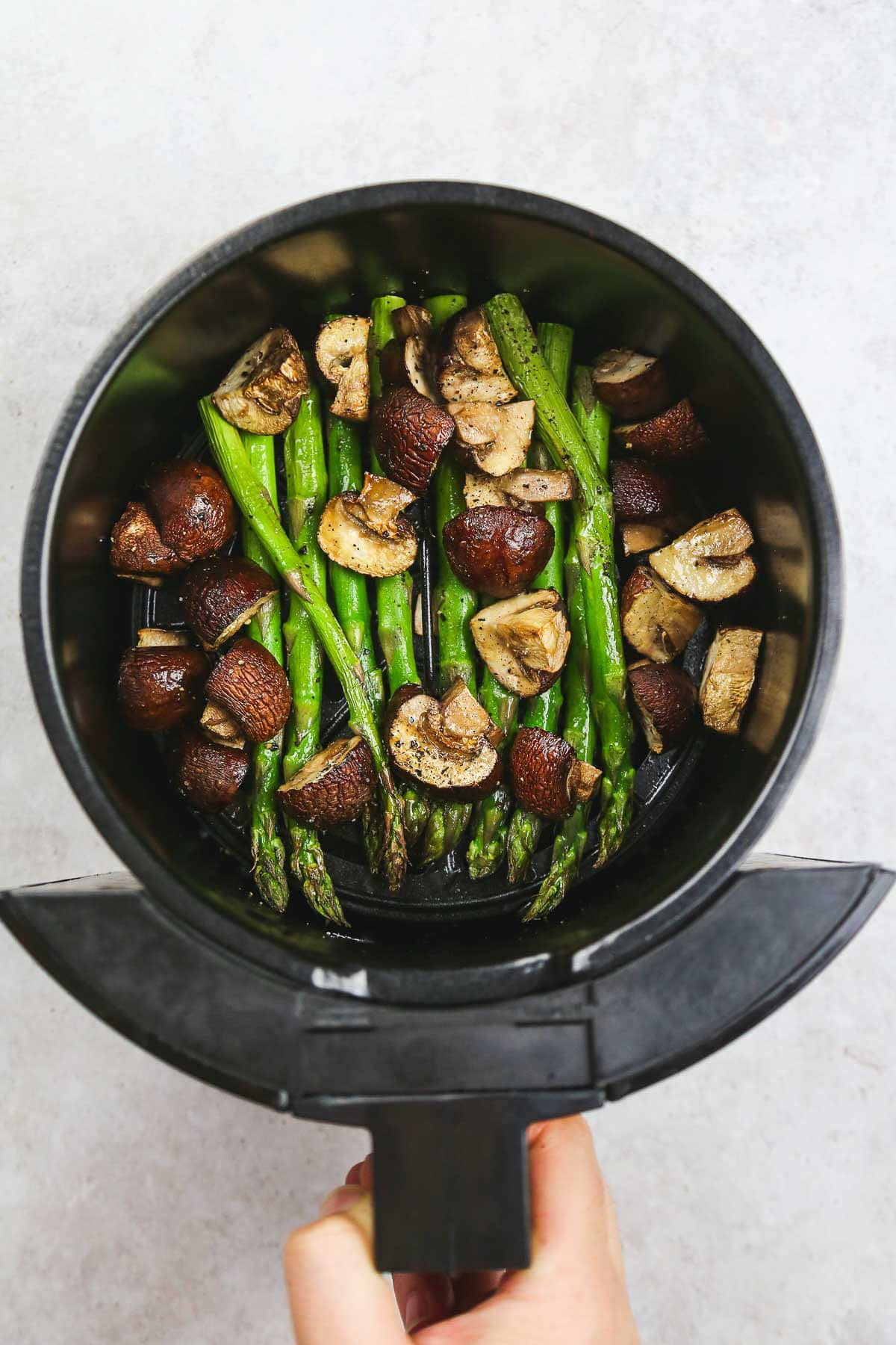 Ready and crispy asparagus and mushrooms in the air fryer basket.