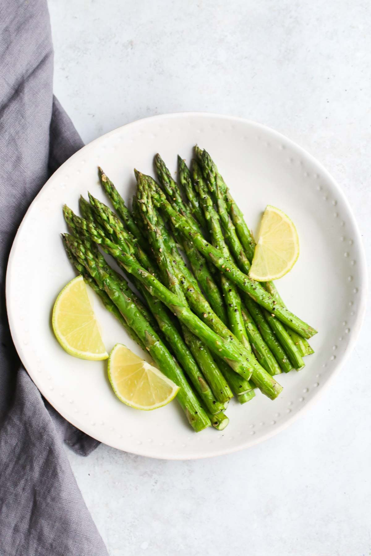Crispy air fryer asparagus served with lemon wedges on a white plate.
