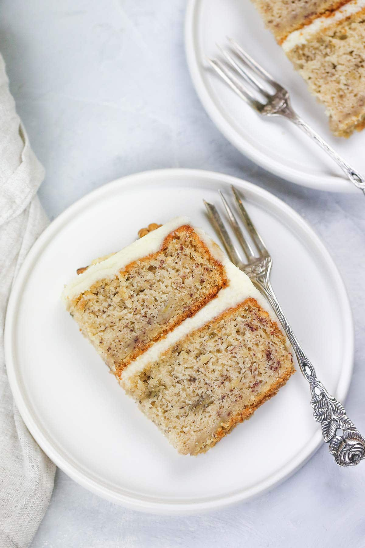A slice of frosted banana cake on a white plate with a cake fork