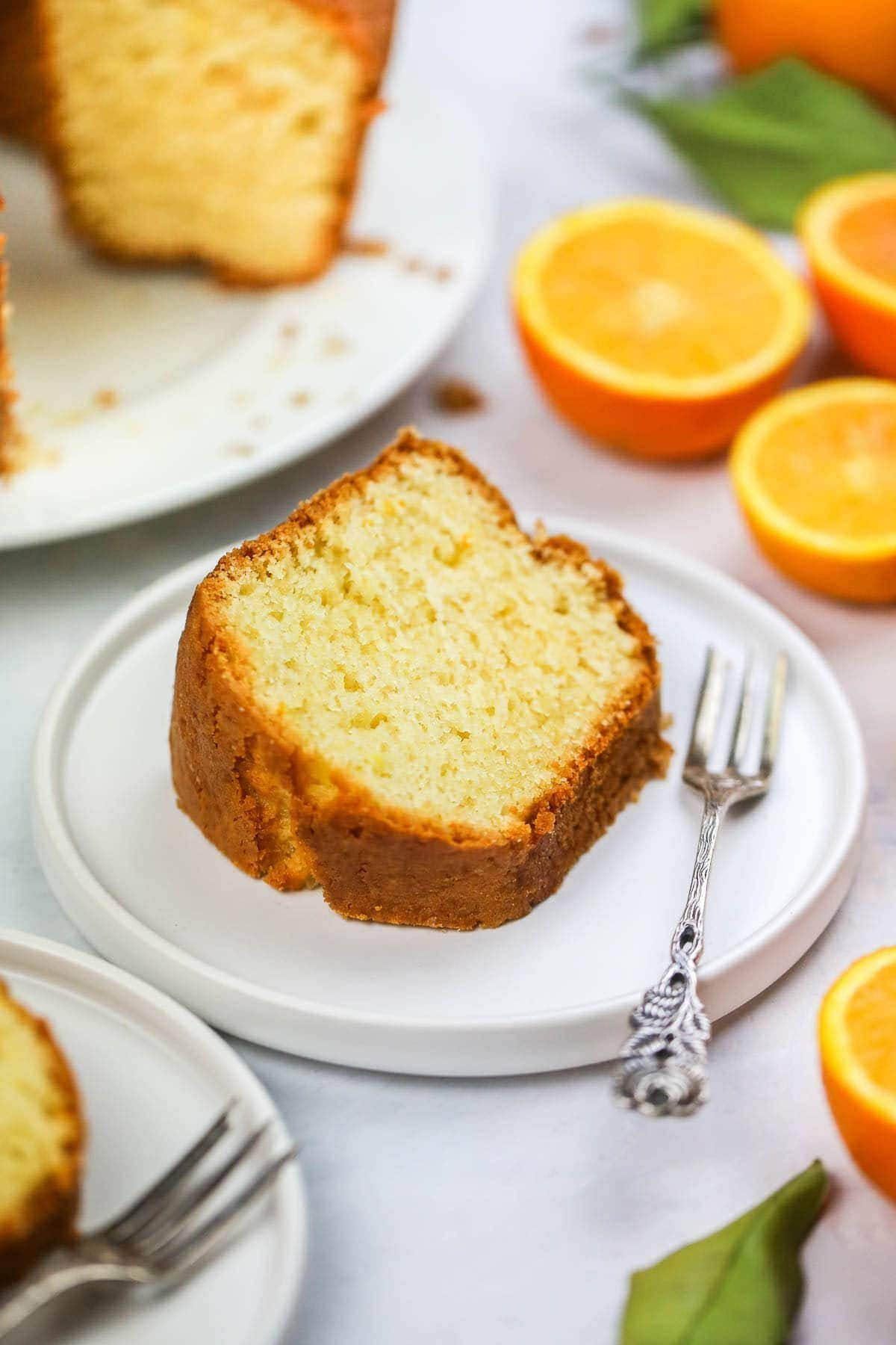 A slice of Orange Juice Cake on a white plate with a vintage cake fork