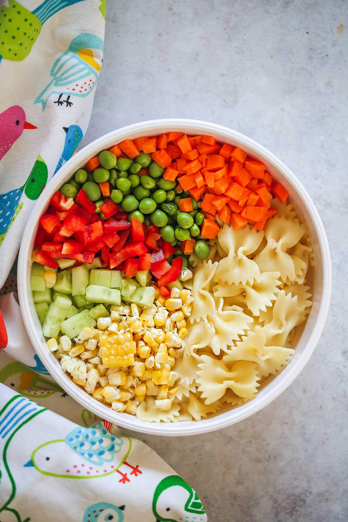 The ingredients of the pasta salad layered in a white bowl, and a bird pattern kitchen towel around it