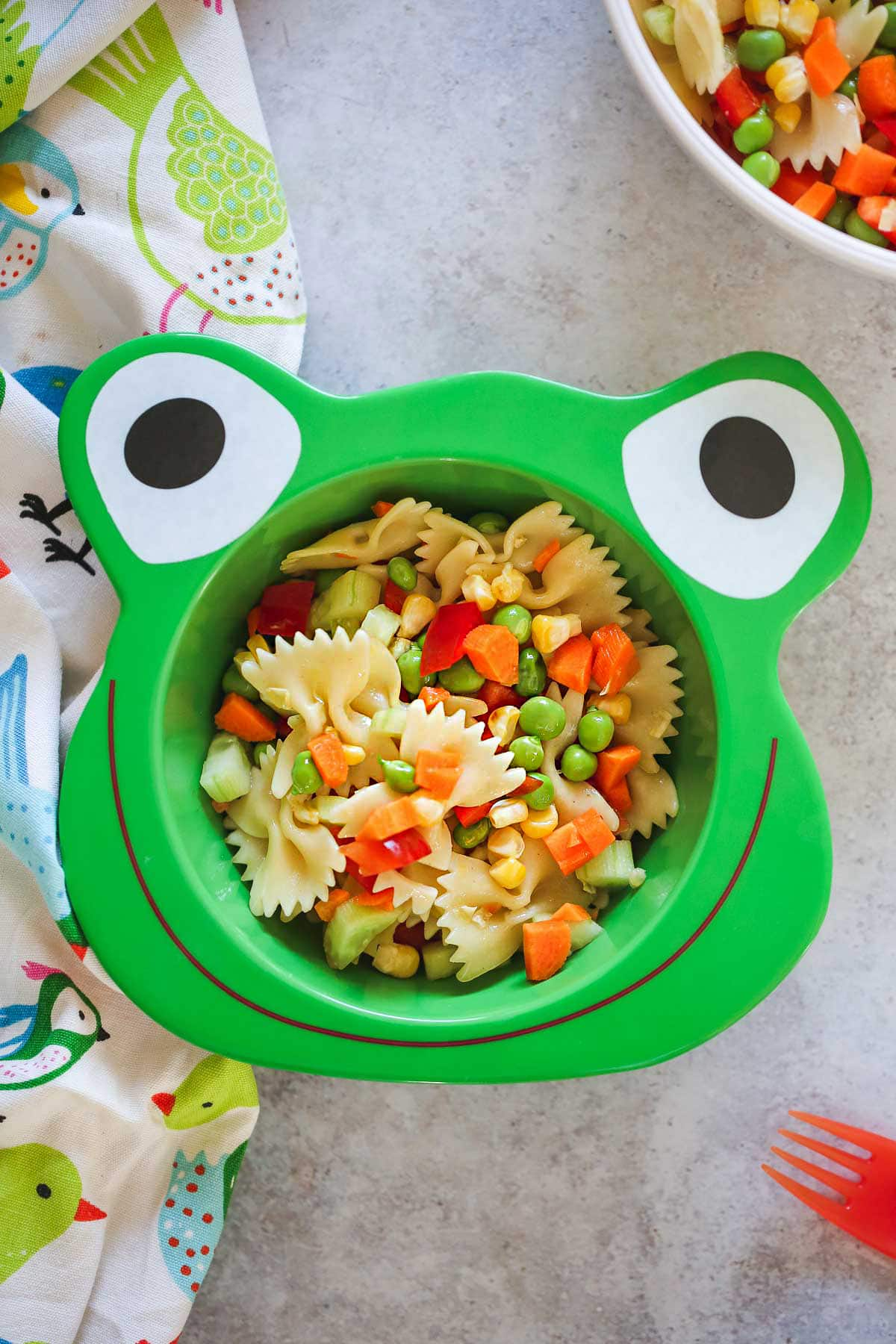 Pasta salad in a fun kids frog shaped bowl and a plastic red fork on the side