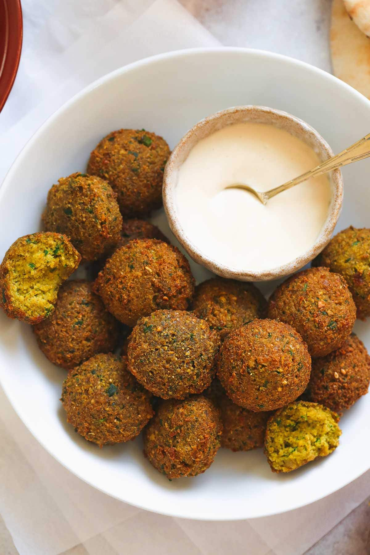 A close up picture of traditional round falafel balls in a bowl with tahini sauce