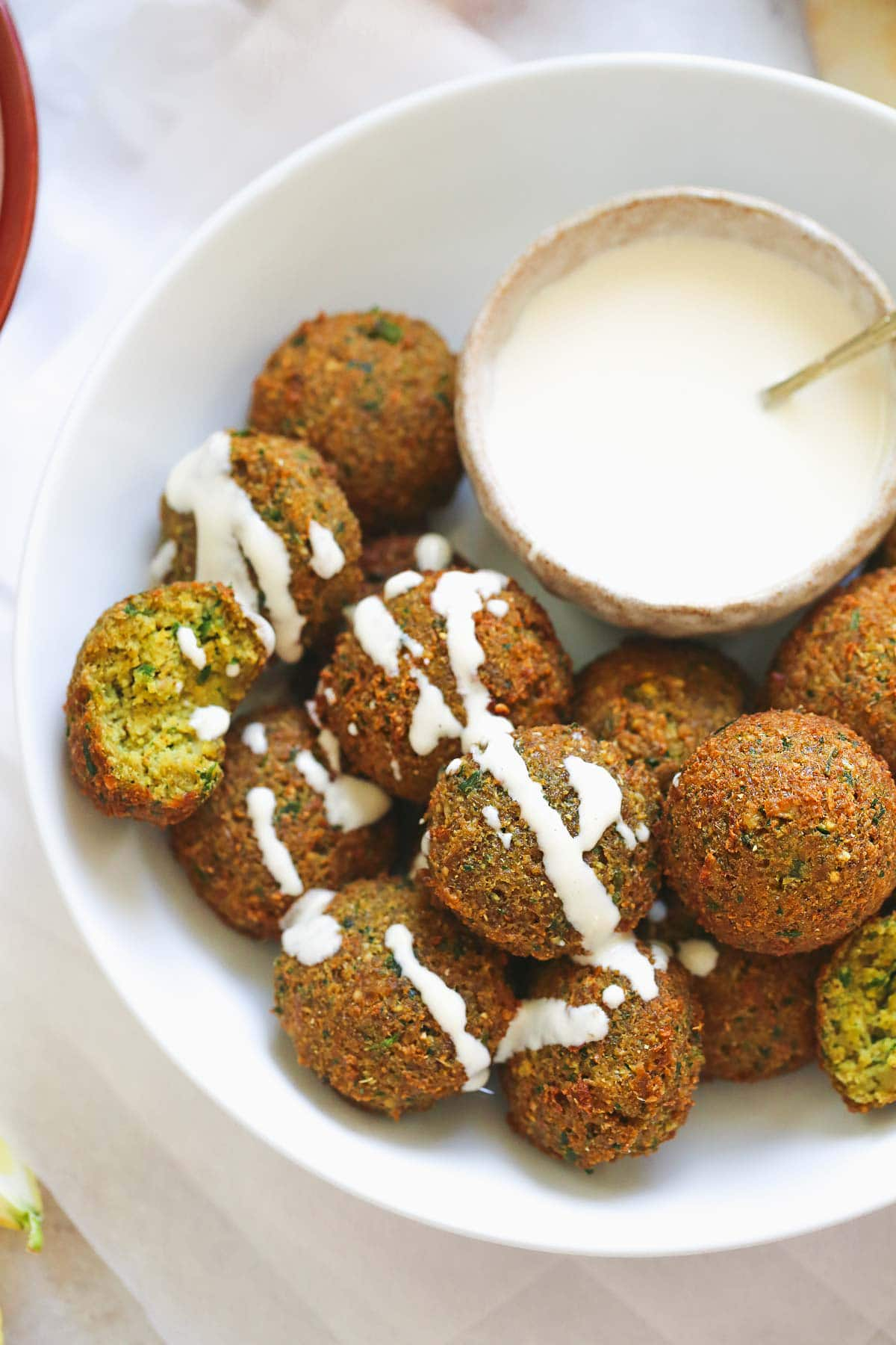 falafel with tahini sauce drizzled over the falafel balls