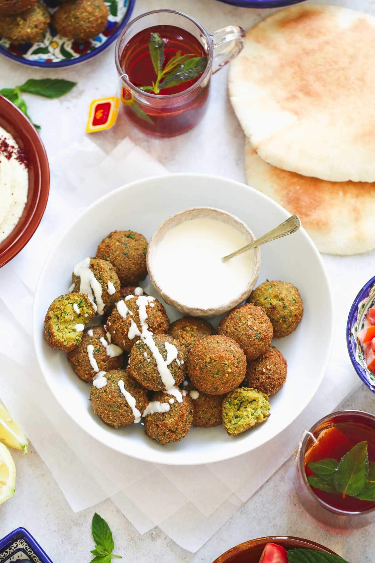 falafel spread with tahini sauce, mint tea, and pita bread.