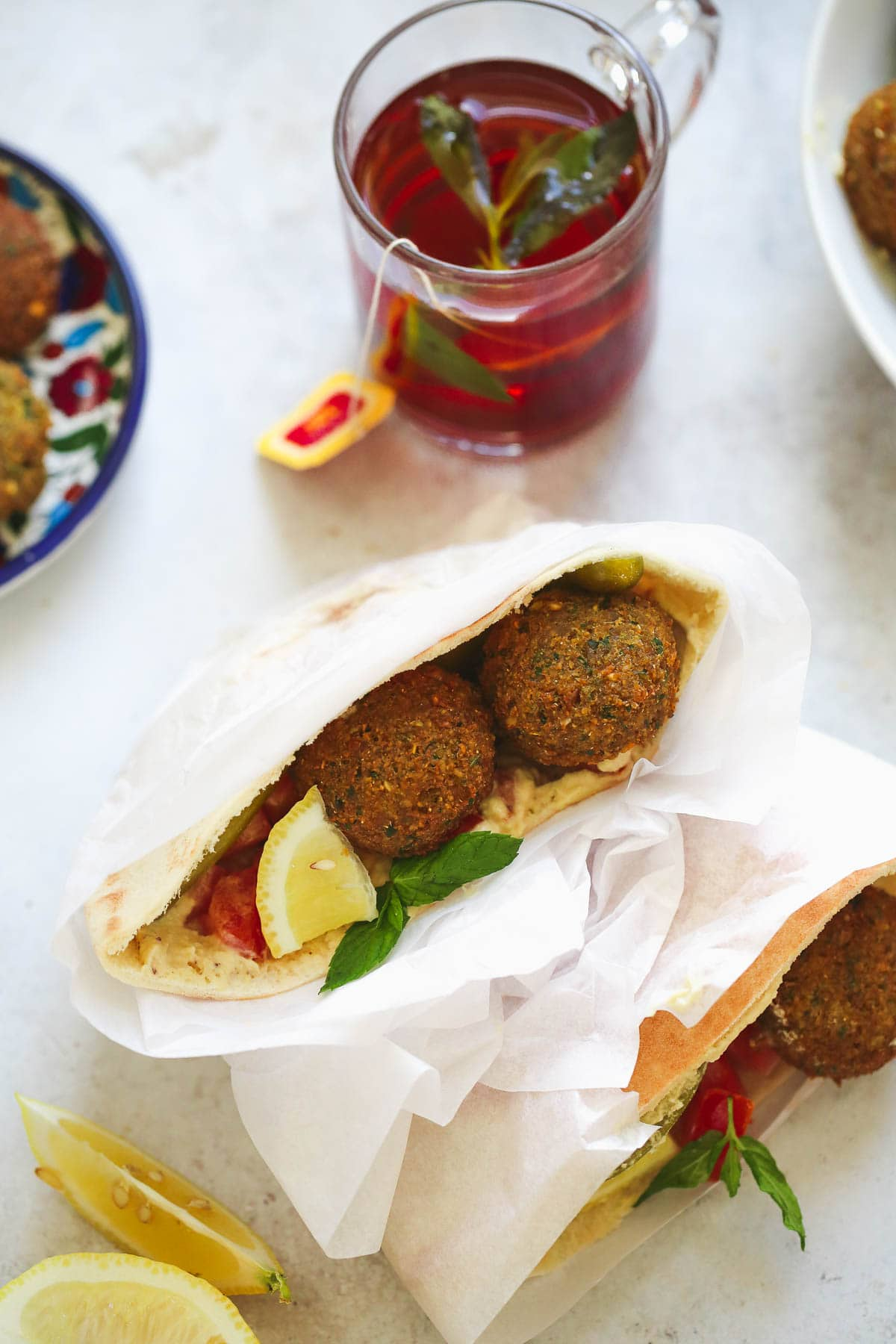 Falafel sandwiches in pita bread wrapped. Garnished with fresh lemon wedges and fresh mint leaves.
