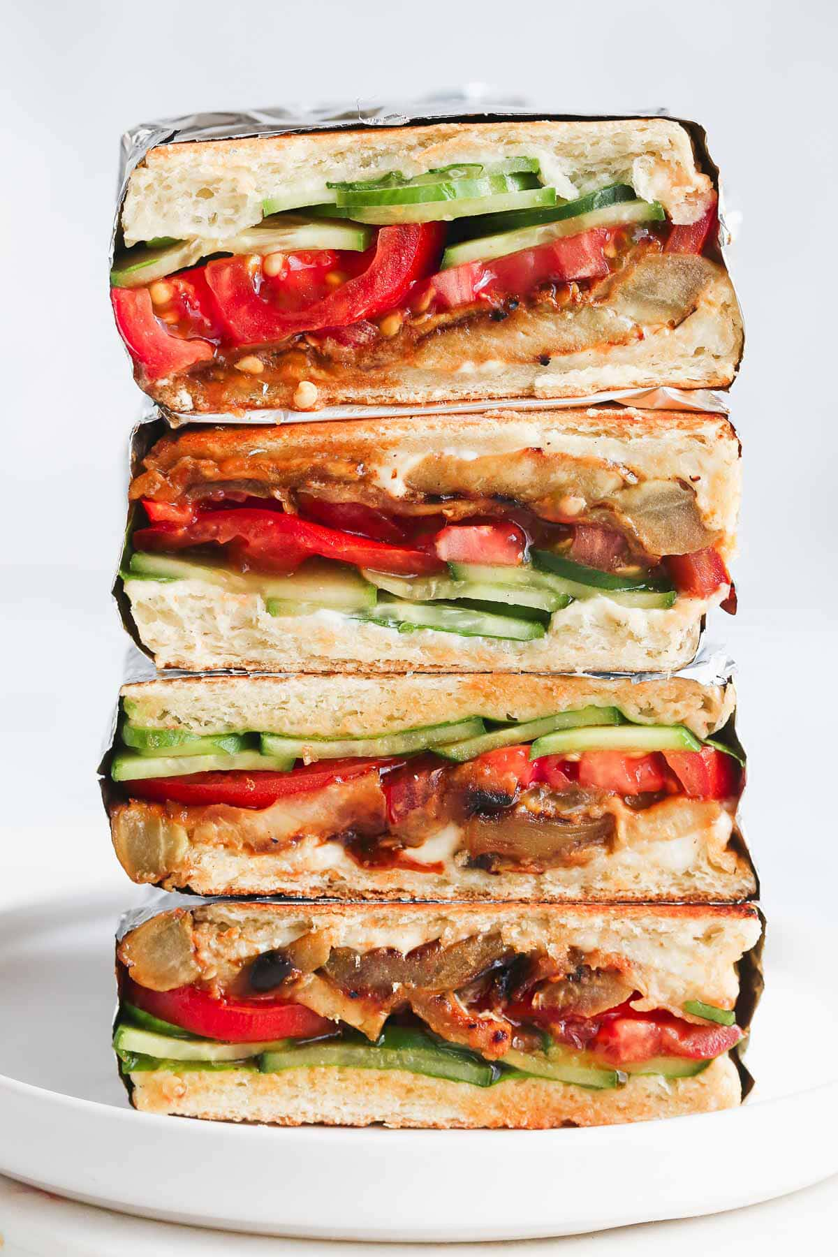 Vegan Eggplant Sandwiches stacked on a white plate