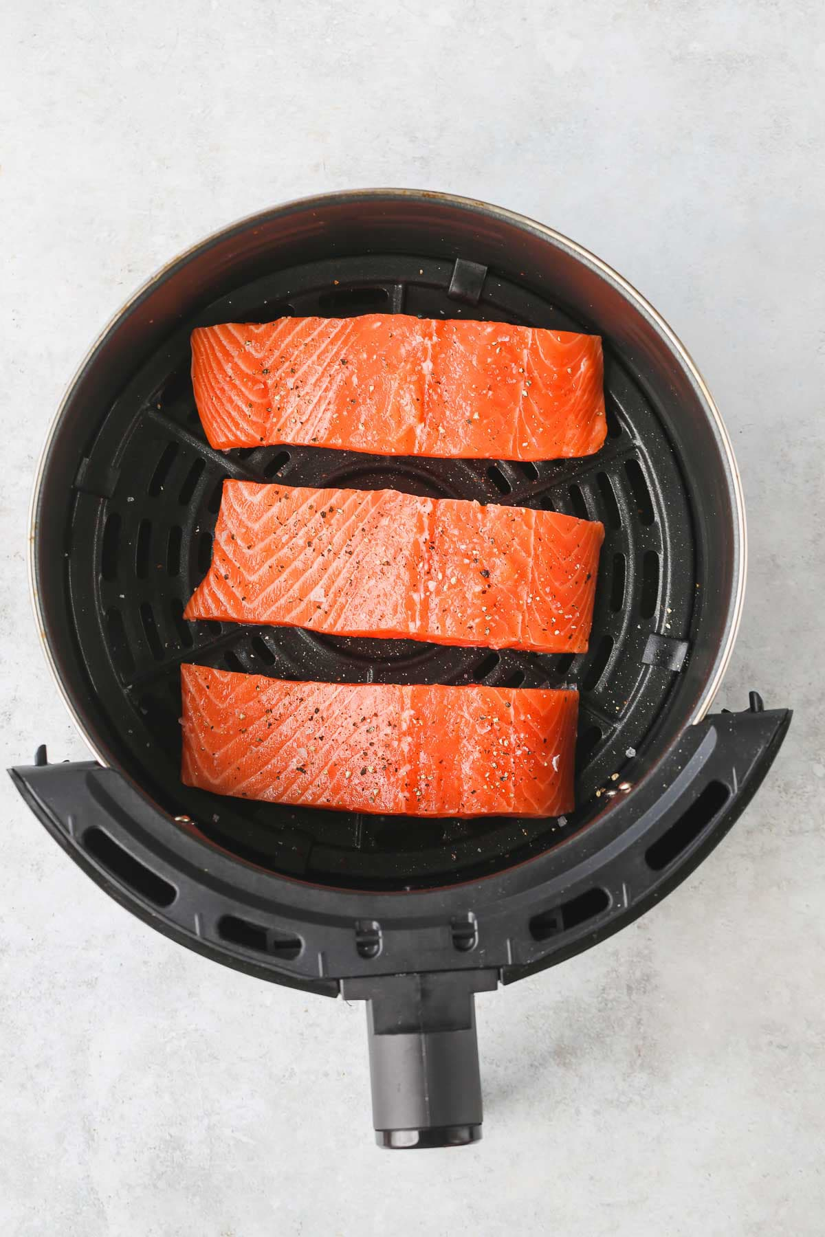 Top view of an air fryer basket with three raw salmon fillets (before cooking).