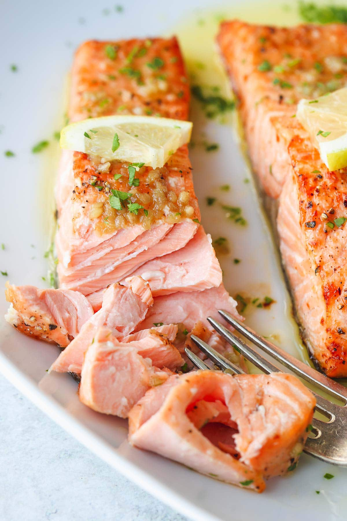 A close up shot showing the flaky air fryer salmon with a fork.