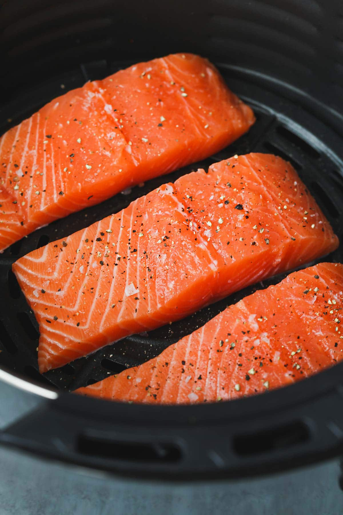 Raw air fryer salmon fillets seasoned and placed in the air fryer basket.
