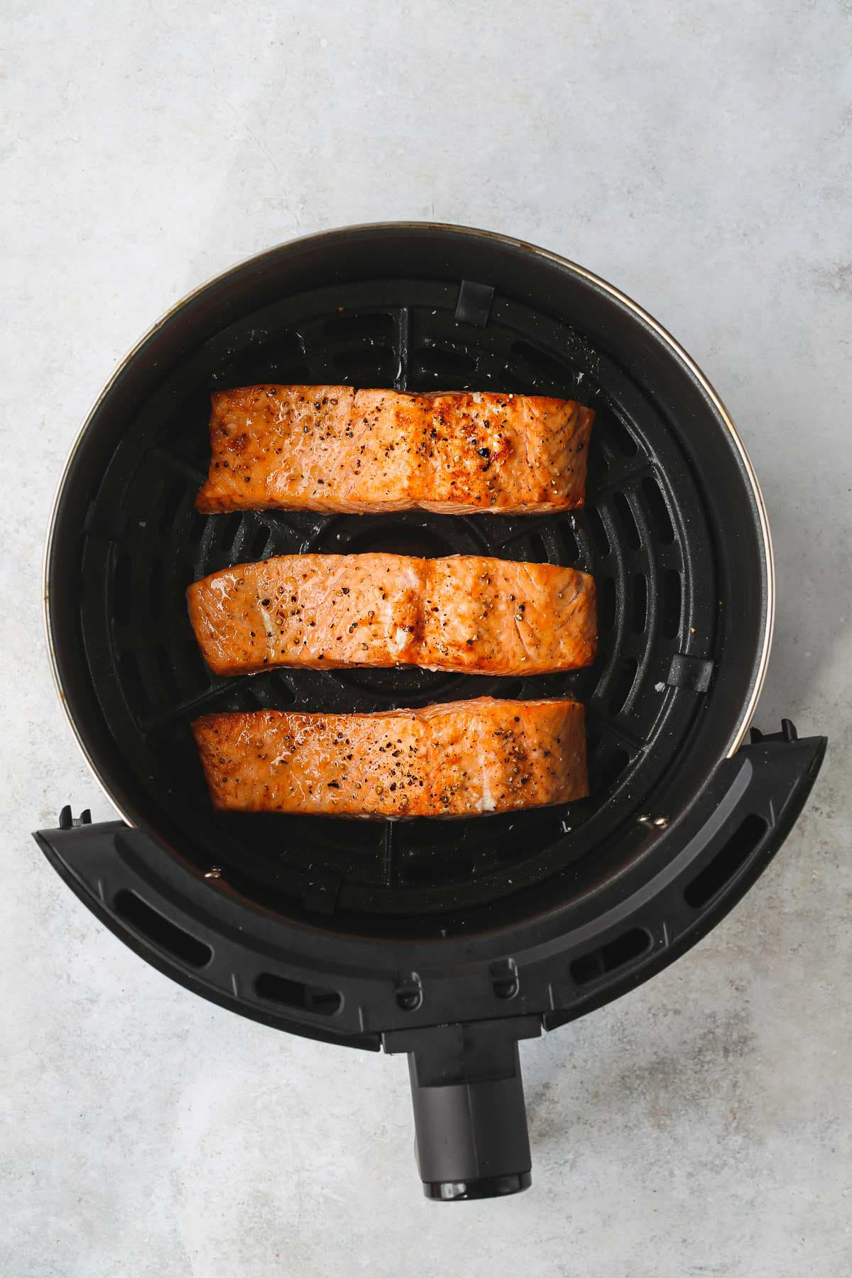 Three air fryer salmon fillets cooked and ready, in the air fryer basket.