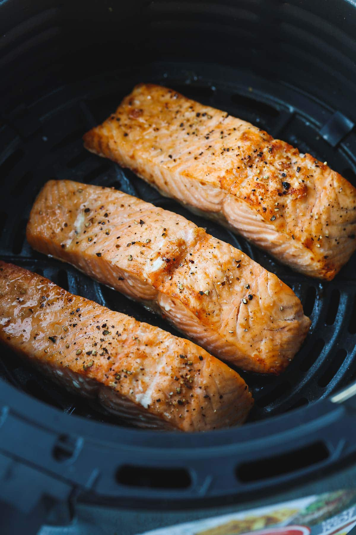 A close up shot of three cooked salmon fillets in the air fryer basket.