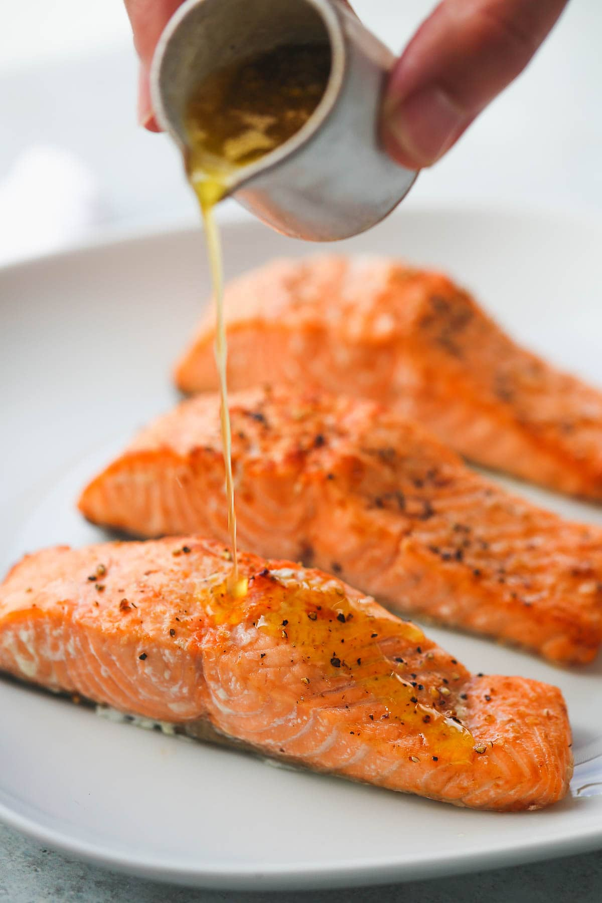 Pouring garlic lemon butter sauce over perfectly cooked air fryer salmon fillets.