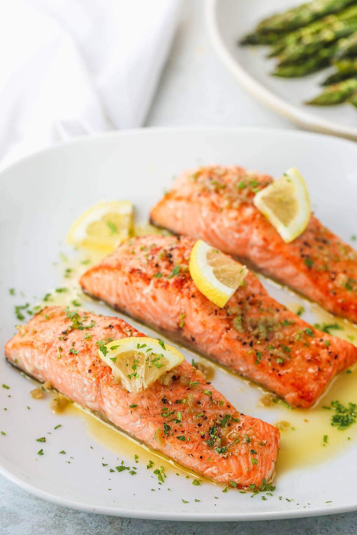 Three air fryer salmon fillets topped with a slice of lemon and chopped parsley on a white plate.