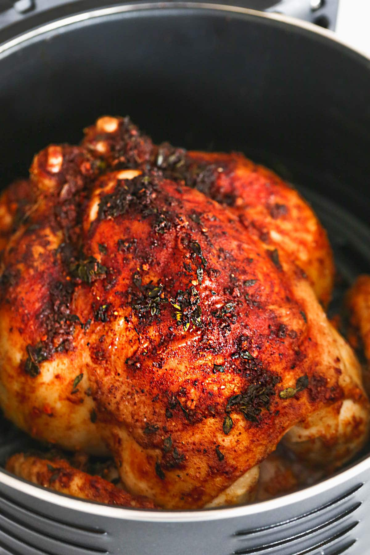 A close up shot of the air fryer rotisserie style chicken in an air fryer
