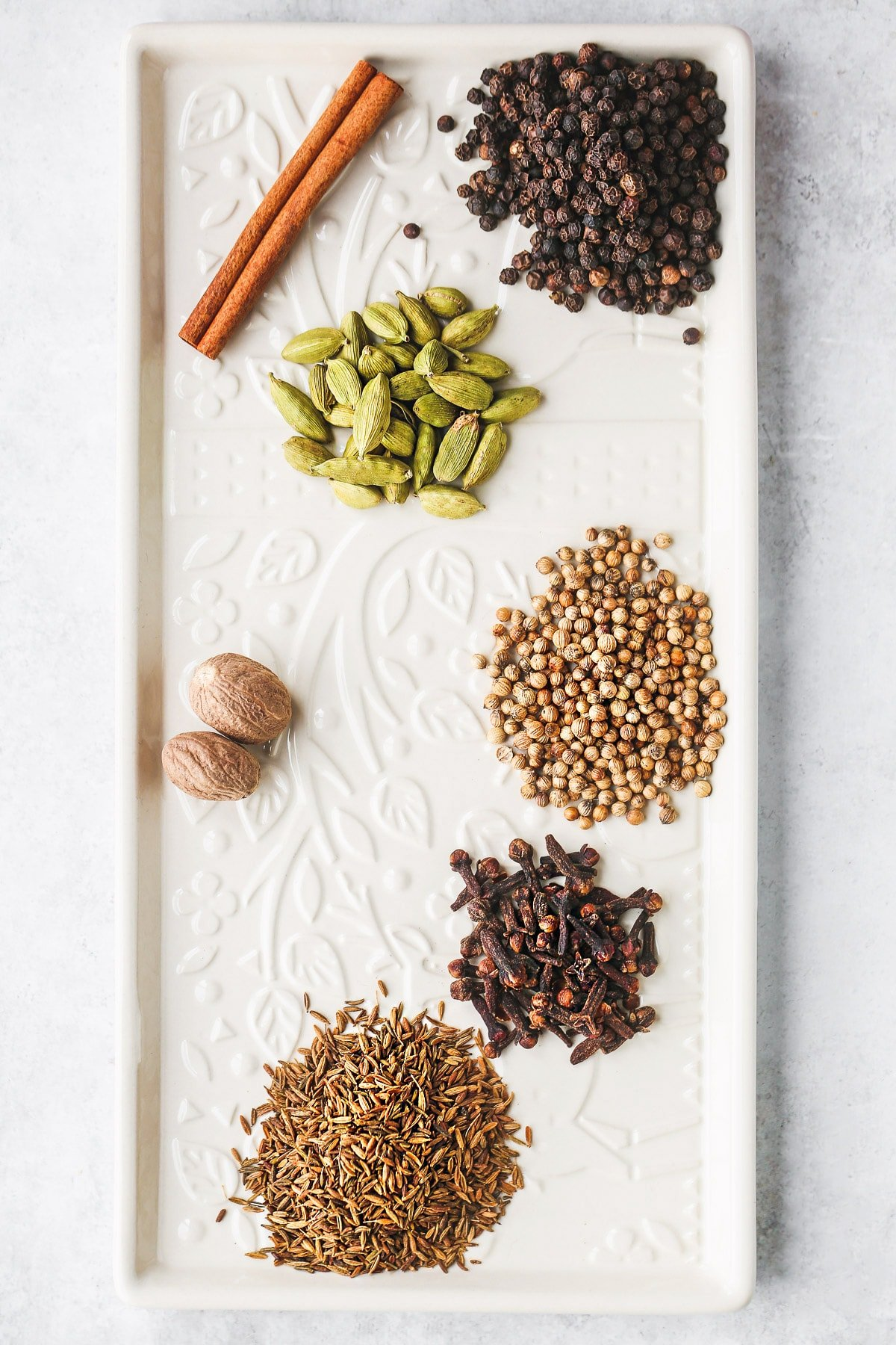 Baharat ingredients on a white glass tray