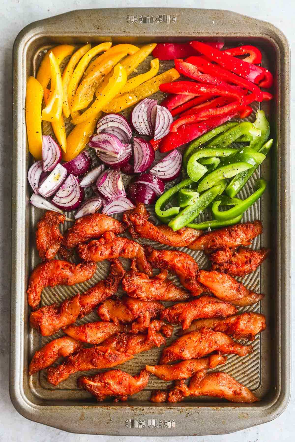 Raw seasoned chicken fajitas and vegetables on a sheet pan