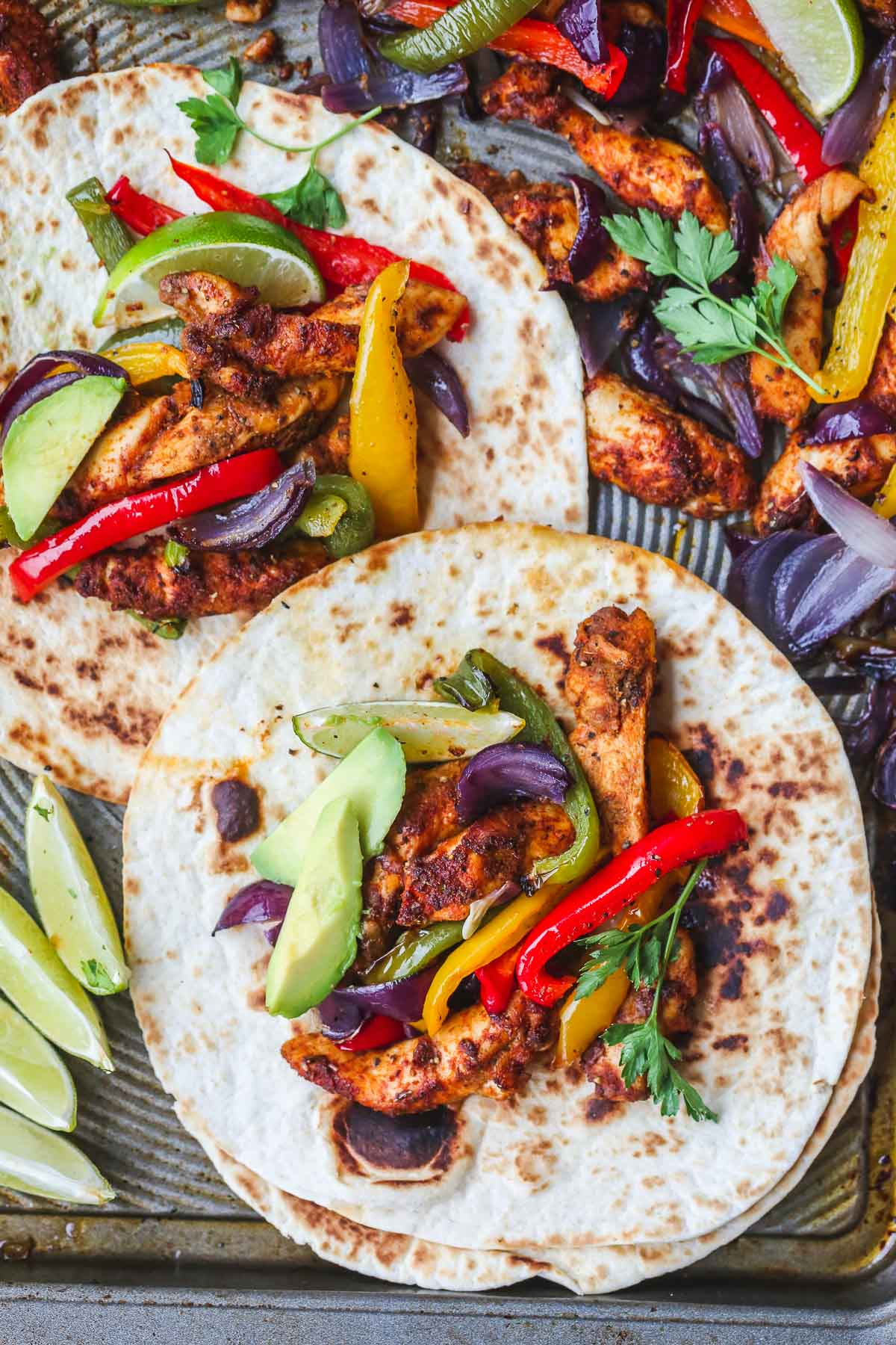 Baked Chicken Fajitas on a sheet pan with tortilla bread and avocado slices
