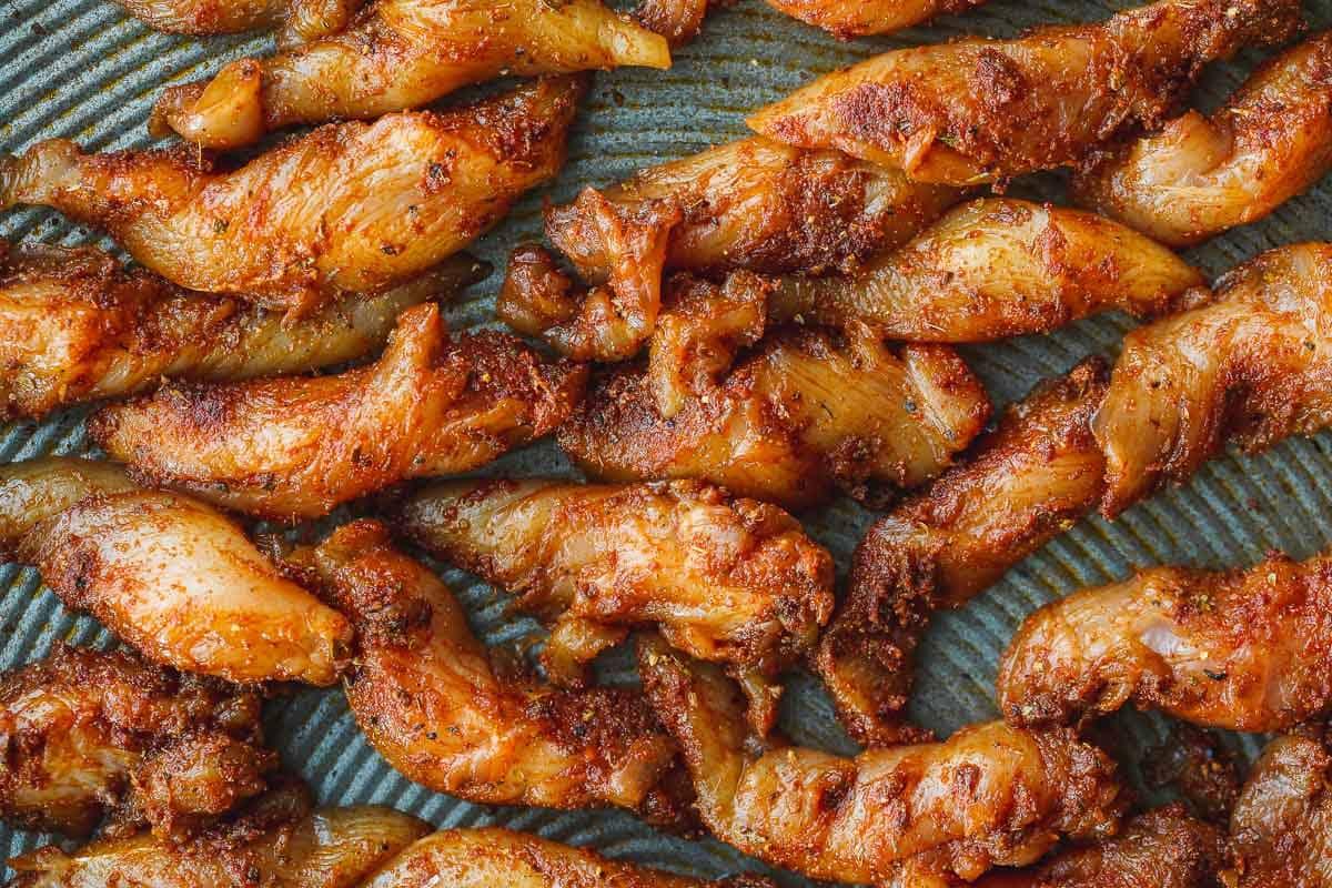 Seasoned chicken fajita strips on a sheet pan.
