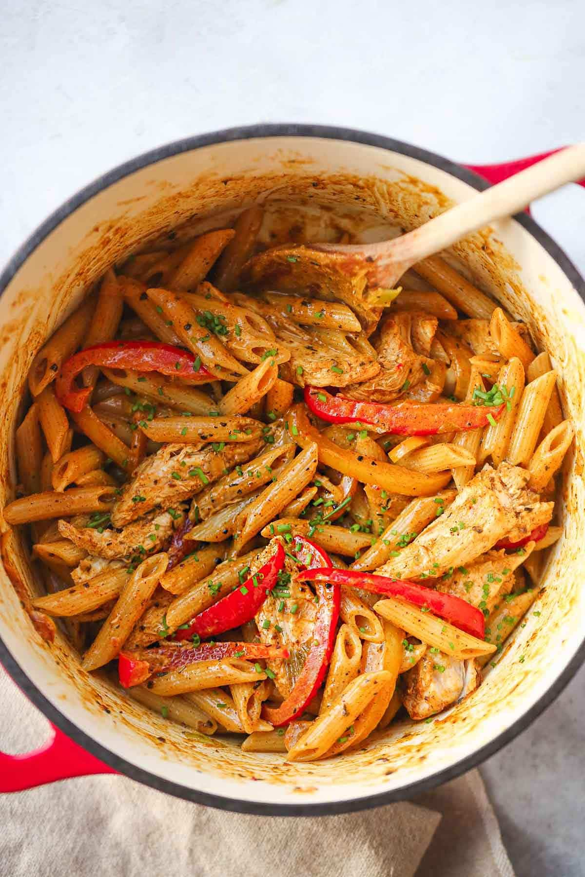 Rasta Pasta in a red cast iron pot with a wooden spoon
