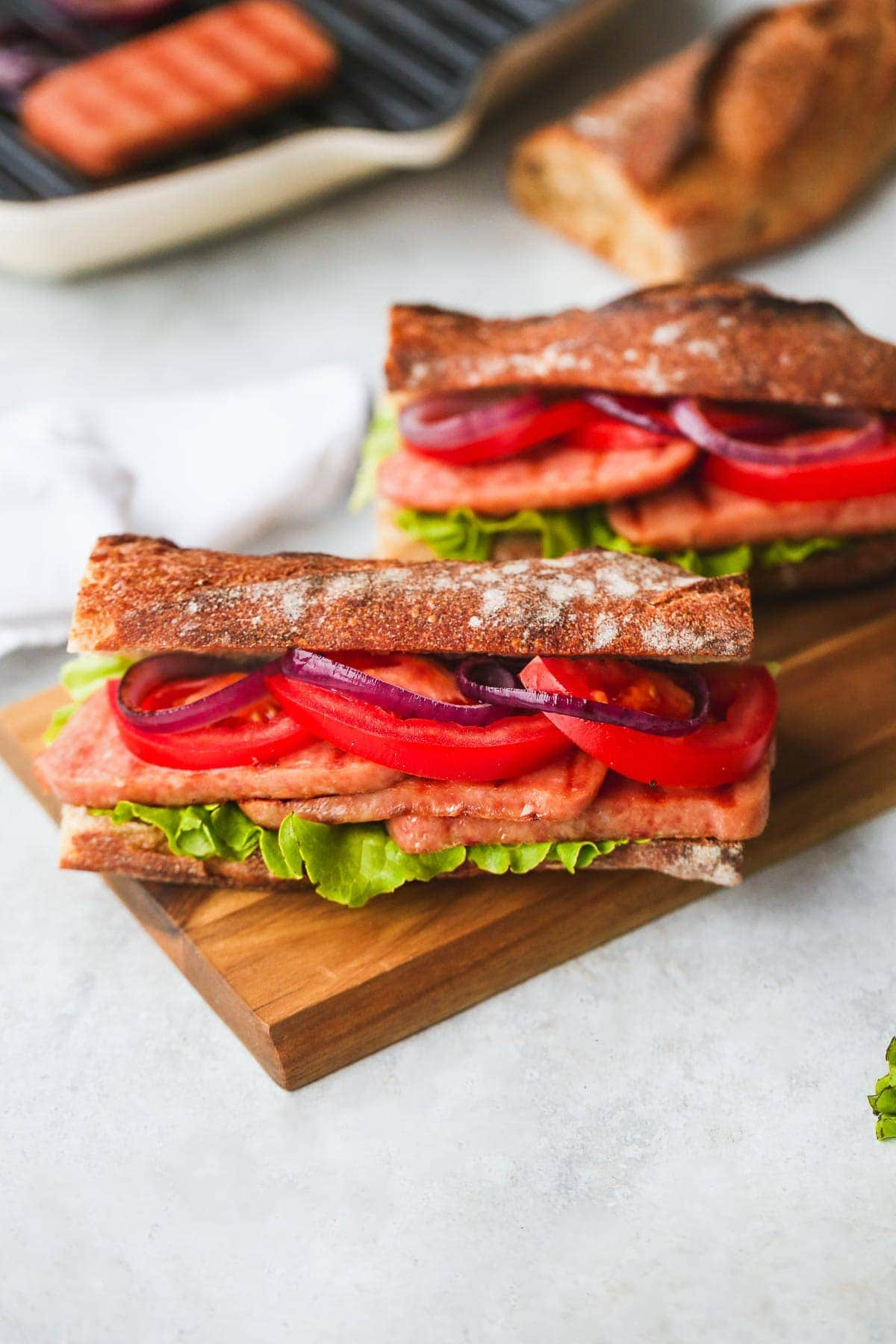 2 grilled SPAM® Steak Sandwiches with tomatoes, lettuce and onions.