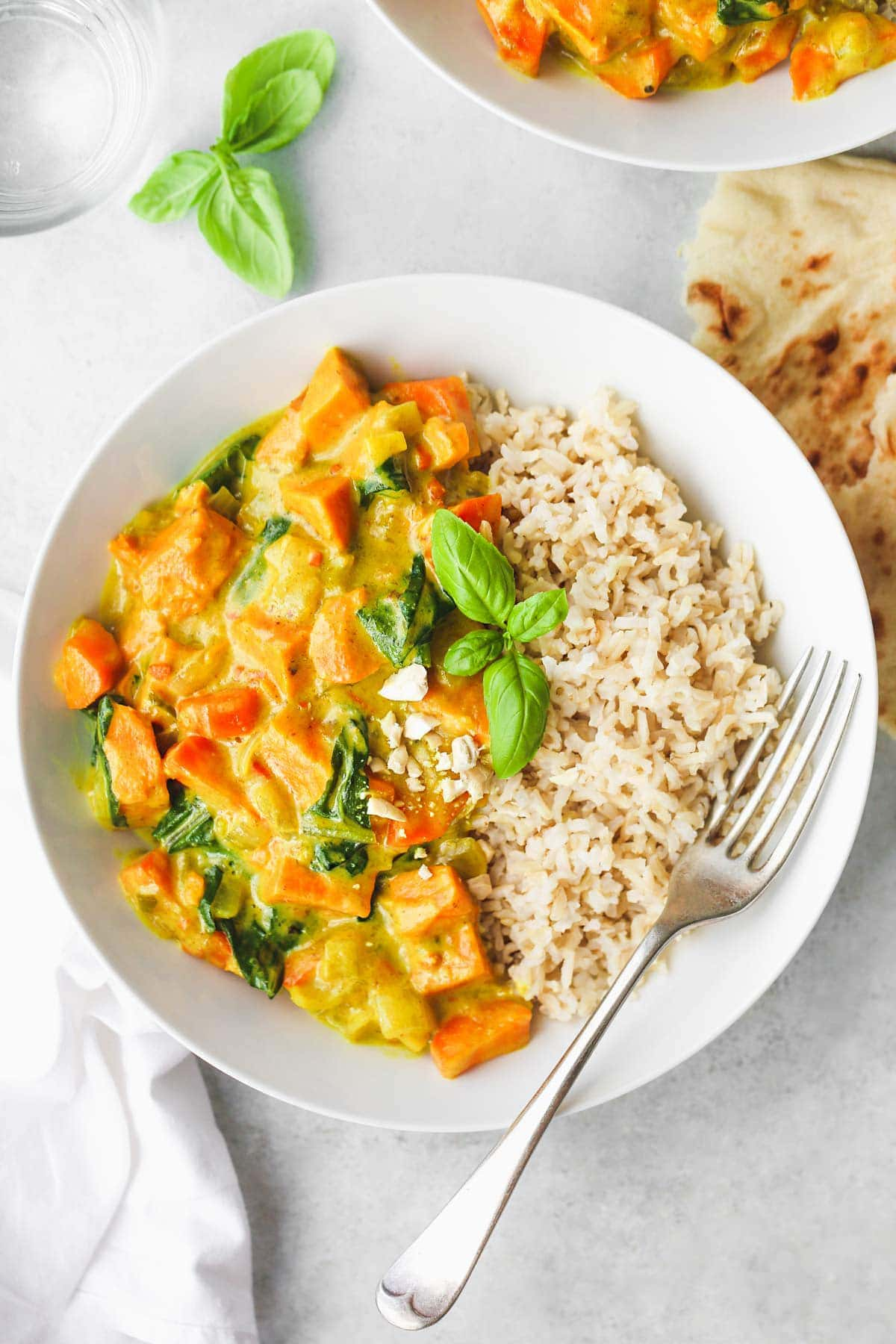 Sweet Potato Curry in a white bowl served with brown rice