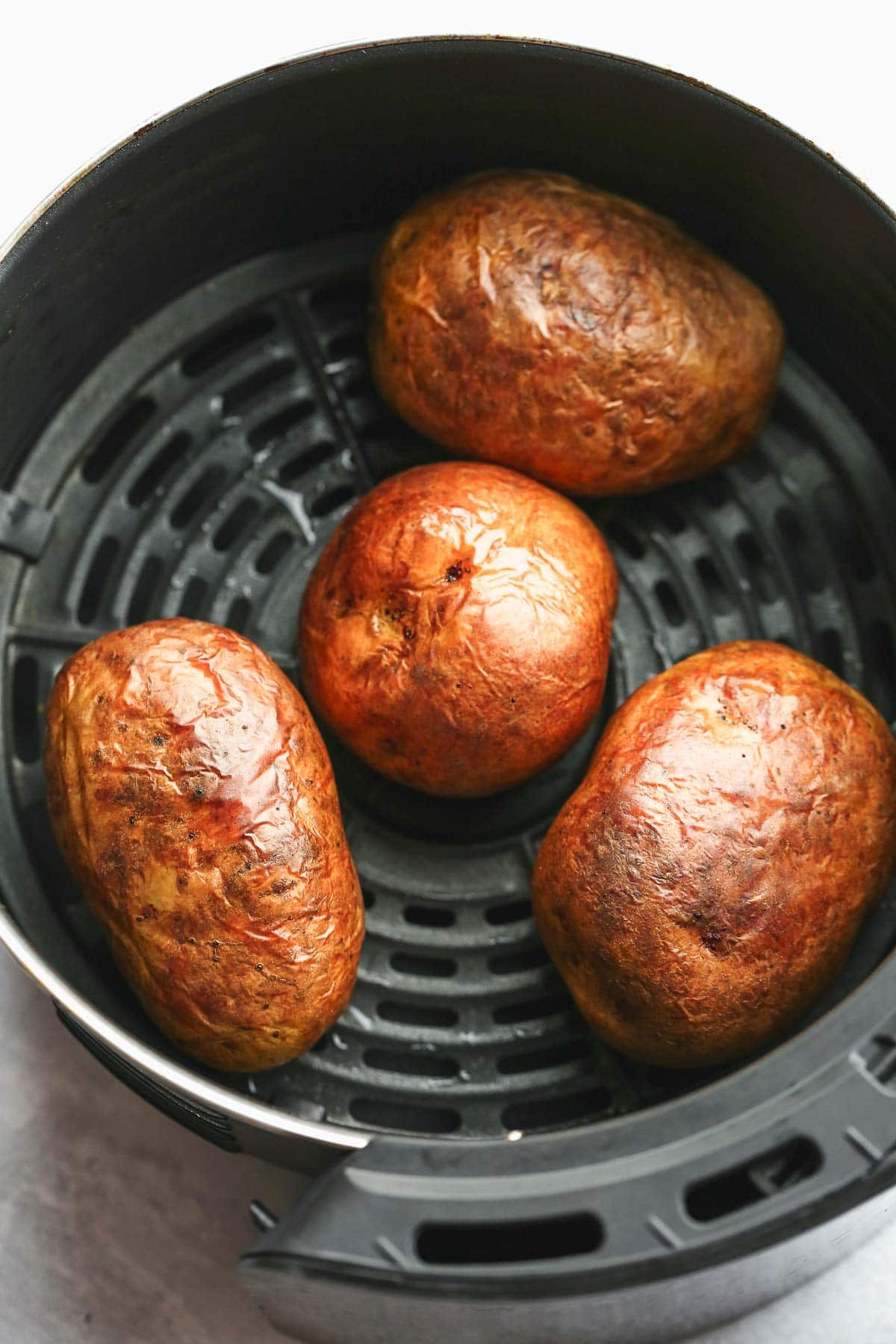 Four golden baked potatoes in the air fryer basket.