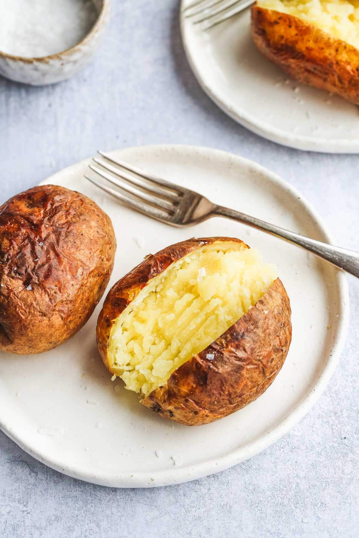 Sliced open air fryer baked potato with its inside fluffed and seasoned with sea salt served on a white plate with a fork. Along with another golden backed potato.