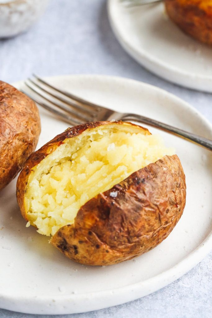 A close up image of air Fryer Baked Potato on a white plate and a fork