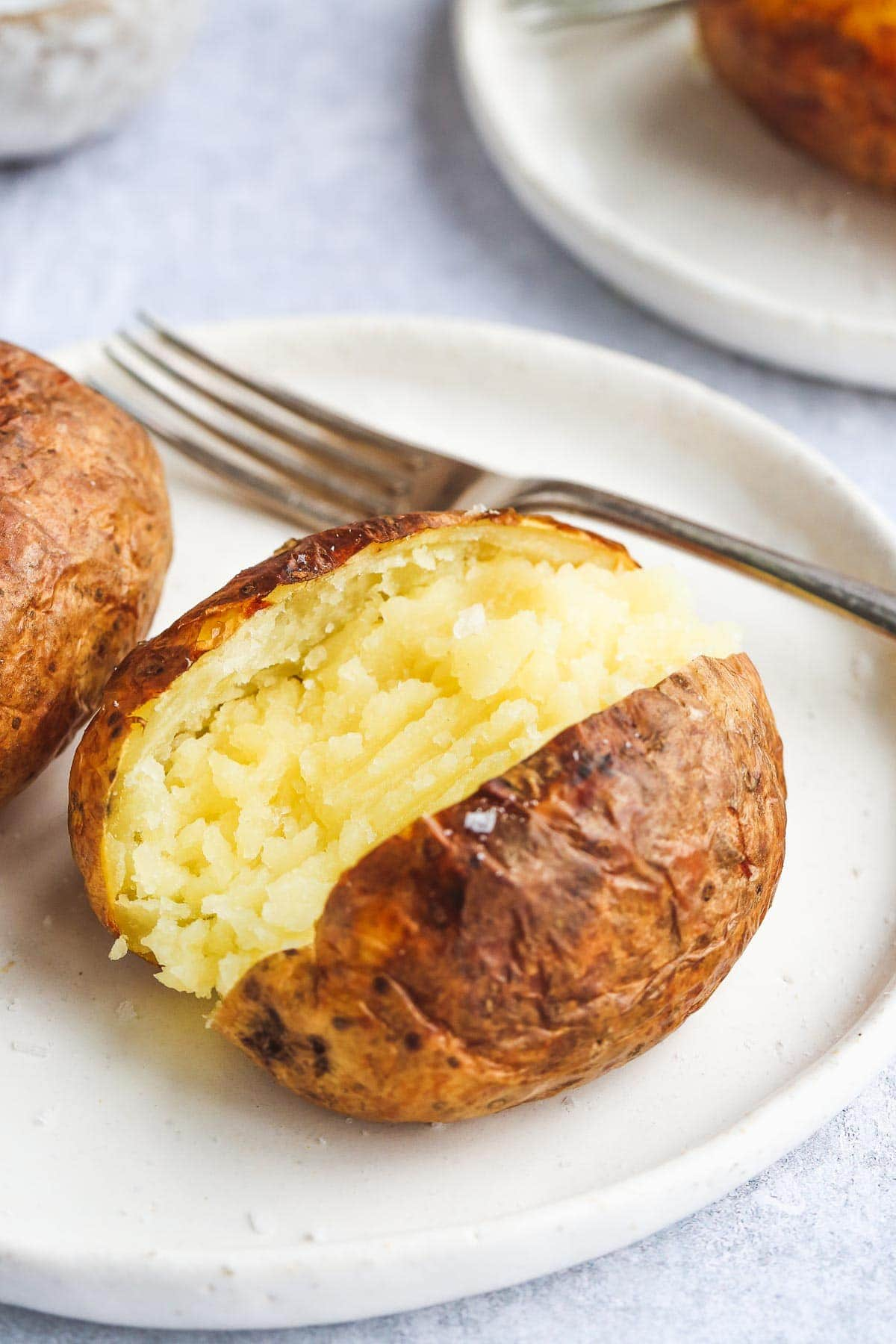A close up image of air fryer sliced open and fluffed baked potato on a white plate and a fork.