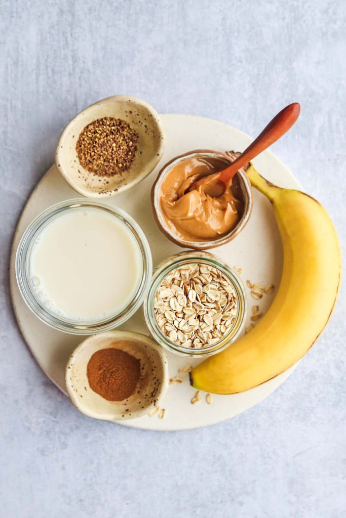 Banana oatmeal smoothie ingredients laid on a tray including a banana, peanut butter, cinnamon, almond milk, ground flaxseed, and oats