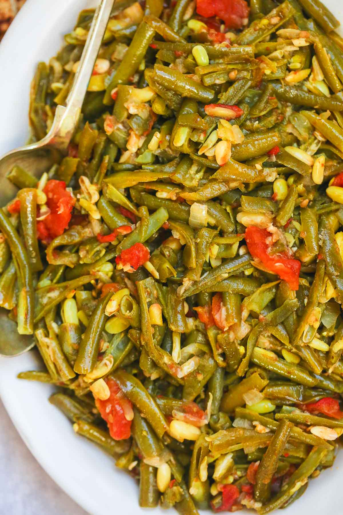 Stewed green beans on a large serving plate and a serving spoon