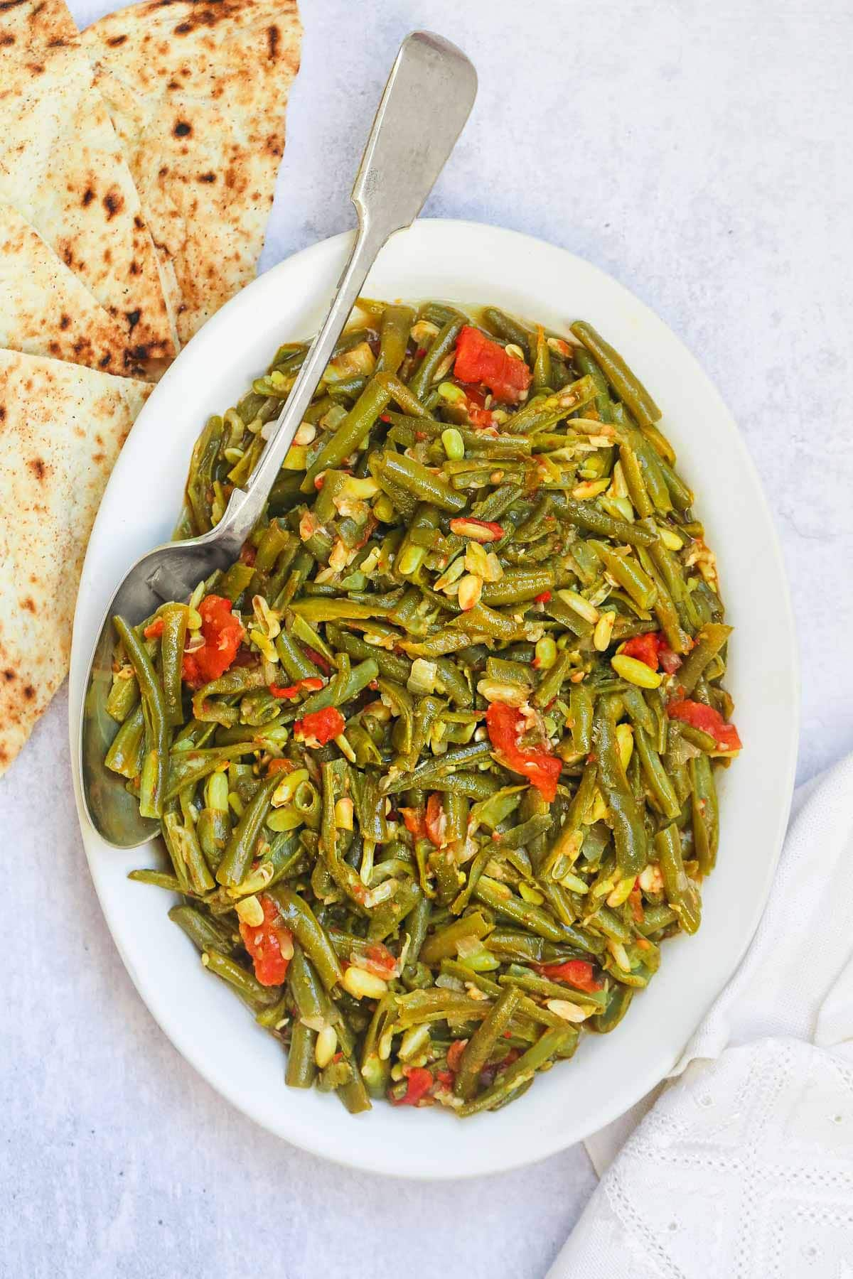 Stewed green beans on a large serving plate and a serving spoon, and pita bread on the side.